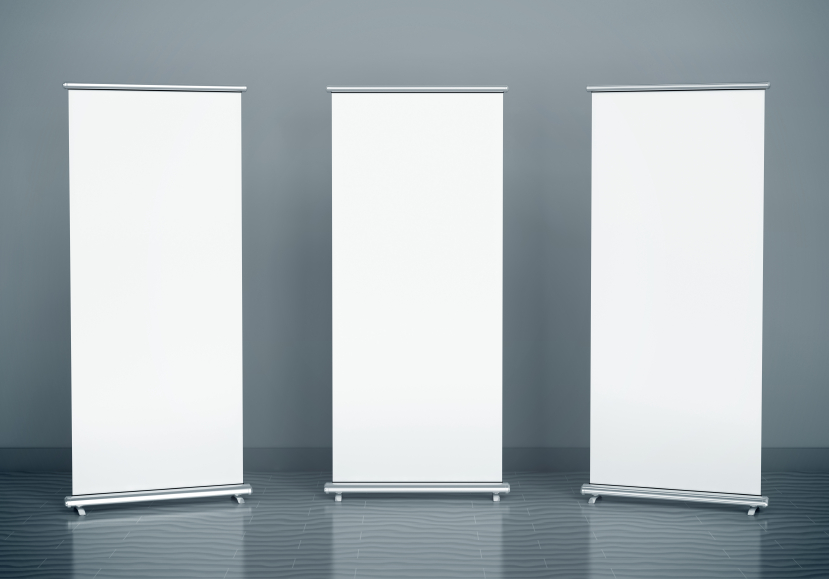 Blank roll-up banners against the grey wall
